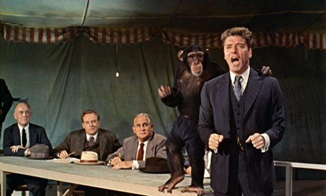 Elmer Gantry (Burt Lancaster) mit einem Affen an seiner Seite bei einem Auftritt im Predigt-Zelt