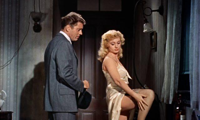 Elmer Gantry (Burt Lancaster) im Anzug neben einer leicht bekleideten Frau, die sich über ihr Bein streicht