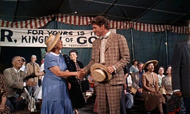 Elmer Gantry (Burt Lancaster) schüttelt im Predigtzelt einer älteren Frau die Hand