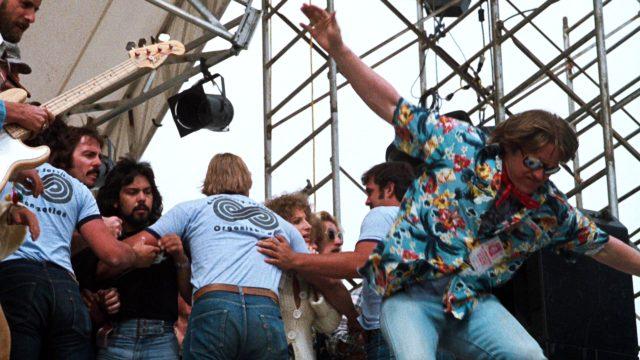 Gary Busey als Musik-Manager Bobbie Ritchie im Bühnengetümmel während eines Konzerts