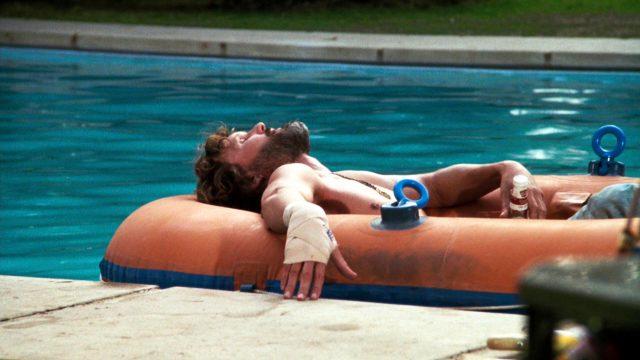 John Norman Howard (Kris Kristofferson relaxt in einem Schlauchboot in seinem Pool)