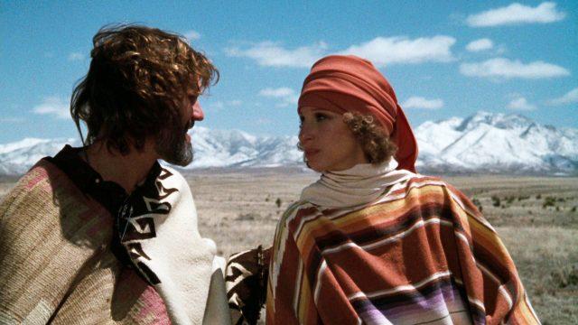 John Norman Howard (Kris Kristofferson) und Esther Hoffman (Barbra Streisand) stehen in freier Natur vor dem Horizont eines Bergmassivs