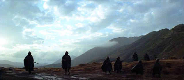 bewaffnete Soldaten in Regencapes schreiten eine matschige Bergebene entlang