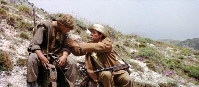 die beiden Männer, inwzischen bewaffnet, rasten an einem felsigen Hang