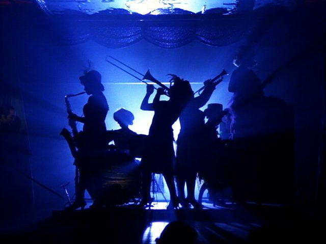 blau ausgeleuchtete Silhouette des Nachtclub-Orchesters während der Show