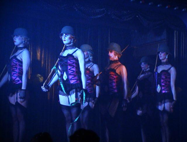 """Bühnenshow im Berliner """"Kit Kat Club"""" mit Tänzerinnen, die Stahlhelme tragen und einen Stechschritt imitieren"""