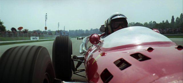 Rennwagen auf der Strecke im Rennen, die Kamera zeigt auf den Fahrer, Copyright: Turner Entertainment