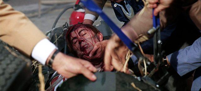 Scott Stoddard (Brian Bedford) blutüberstrohmt und ohnmächtig im Cockpit seines verunglückten Rennwagens