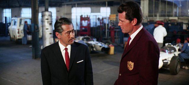 Toshiro Mifune als Izo Yamura in seiner Rennwagenwerkstatt im Gespräch mit Pete Aron (James Garner)