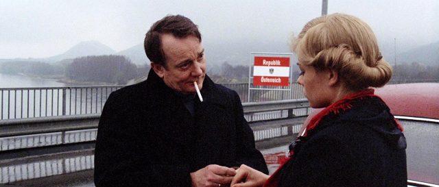 Denholm Elliott als Stefan Vognic mit Zigarette im Mund im Gespräch auf einer Brücke an der Grenze zum Ostblock