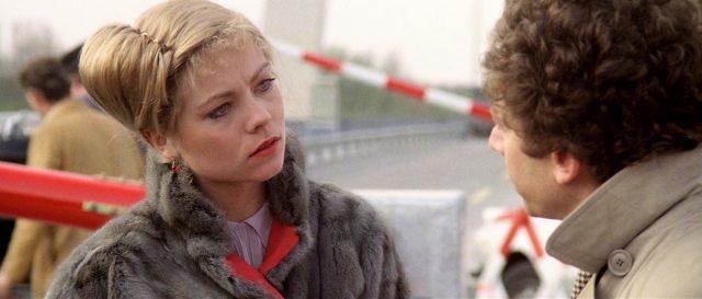 Milena Flaherty (gespielt von Theresa Russell), gekleidet in einem Pelzmantel, mit ernster Miene im Gespräch auf einer Brücke an der Grenze zum Ostblock