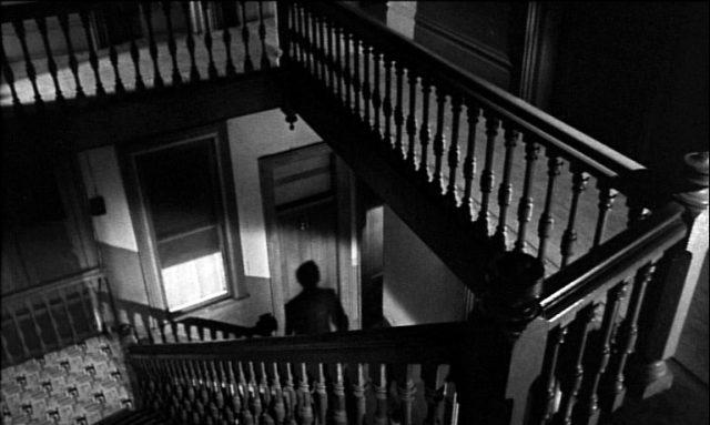 ein düsteres Treppenhaus, in dem der Schatten einer Person zu erkennen ist