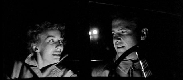 Christina Bailey (gespielt von Cloris Leachman) und Mike Hammer (gespielt von Ralph Meeker) unterwegs im Cabrio in der Dunkelheit, im Hintergrund sind die Scheinwerfer eines Fahrzeugs erkennbar