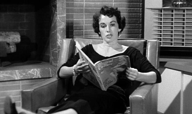 Maxine Cooper als Hammers Assistentin Velda Wickman beim Lesen eines Magazins im Ledersessel
