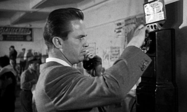 Mike Hammer (gespielt von Ralph Meeker) benutzt ein Münztelefon in einem Box-Gym