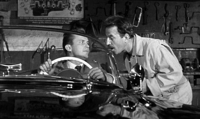 Mike Hammer (gespielt von Ralph Meeker) hinter dem Steuer seines Cabrio im Gespräch mit dem an der Karosserie lehnenden Mechaniker Nick (gespielt von Nick Dennis) in dessen Garage, Copyright: United Artists