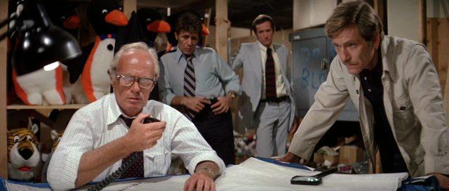 die Taskforce in einem Gebäude eines Freizeitparks, im Vordergrund Hoyt (gespielt von Richard Widmark) und Harry Calder (gespielt von George Segal) über eine Karte gebeugt, Copyright: Universal