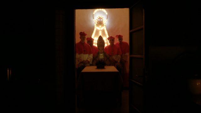 der Papst und einige seiner Kardinäle in einem Raum, betrachtet aus einem dunklen Hausflur