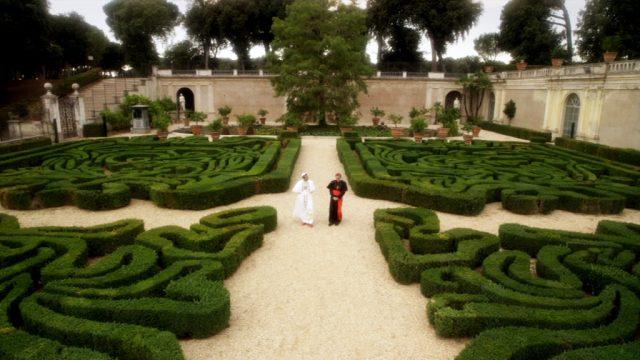Papst Pius XIII. wandelt mit einem seiner Berater durch den Garten des Vatikans
