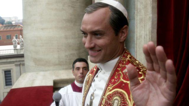 Jude Law als grinsender Papst Pius XIII. bei seiner Rede auf dem Balkon des Petersdomes, Copyright: Wildside, Sky Italia, Haut et Court TV, HBO, Mediapro