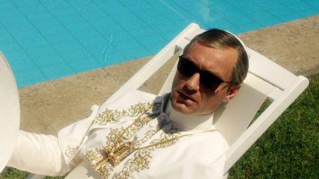 Papst Pius XIII. (gespielt von Jude Law) mit Sonnenbrille auf einer Liege am Swimmingpool, Copyright: Wildside, Sky Italia, Haut et Court TV, HBO, Mediapro