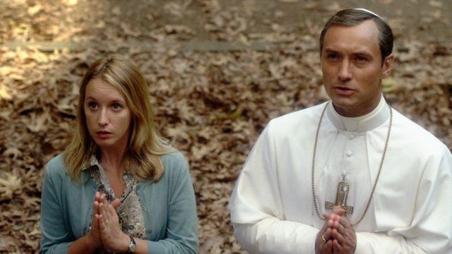 Esther (gespielt von Ludivine Sagnier) und Papst Pius XIII. (gespielt von Jude Law) beim gemeinsamen Gebet auf einer laubbedeckten Wiese