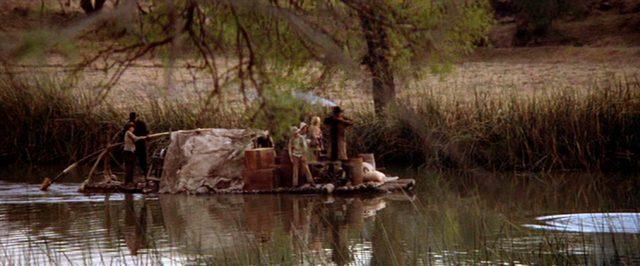 eine Familie fährt auf einem Floß einen Fluss hinab