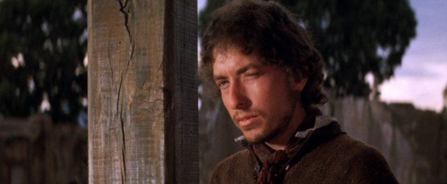 Alias (gespielt von Bob Dylan) steht neben einem vertikalen Holzbalken
