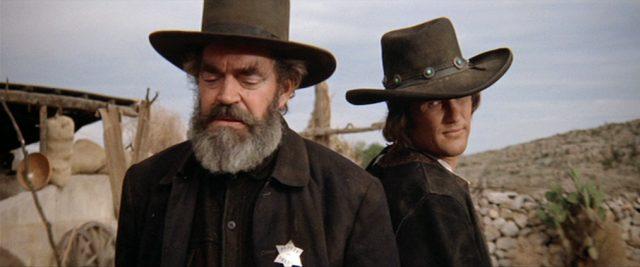 Alamosa Bill (gespielt von Jack Elam) und Billy the Kid (gespielt von Kris Kristofferson) stehen zu Beginn ihres Revolverduells Rücken an Rücken, Copyright: Turner Entertainment, Warner Bros.