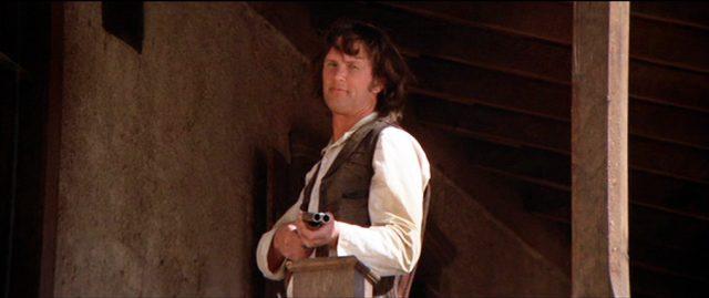 Billy the Kid (gespielt von Kris Kristofferson ohne Bart) steht an einer Brüstung mit doppelläufiger Schrotflinte im Anschlag