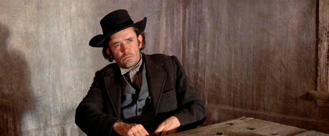 Matt Clarke sitzt als Hilfssheriff J.W. Bell an einem Tisch, Copyright: Turner Entertainment, Warner Bros.