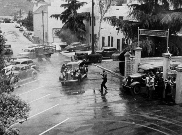 die Gangster brausen vor dem Fabrikgelände in einer Limousine davon, während sie sich mit einem Polizisten einen Schusswechsel liefern, Copyright: Universal