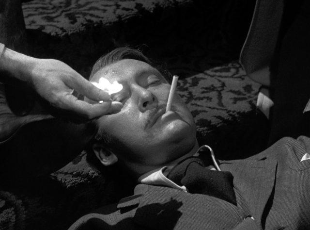 Big Jim Colfax (gespielt von Albert Dekker) liegt sterbend auf den Treppenstufen seiner Villa, während ihm jemand die letzte Zigarette anzündet, Copyright: Universal