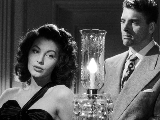 """Kitty Collins (gespielt von Ava Gardner) und Ole """"Swede"""" Anderson (gespielt von Burt Lancaster) stehen nebeneinander, zwischen ihnen leuchtet eine Tischlampe"""