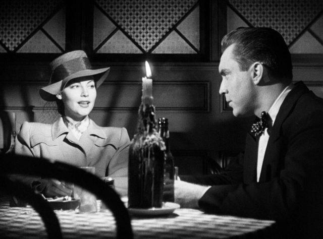 Kitty Collins (gespielt von Ava Gardner) und Jim Reardon (gespielt von Edmond O'Brien) unterhalten sich bei Kerzenschein in einem Restaurant