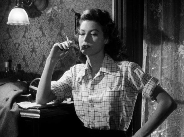 Ava Gardner als Kitty Collins rauchend in einem Appartementzimmer