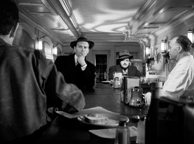 die beiden Auftragskiller Max und Al (gespielt von William Conrad und Charles McGraw) sitzen im Diner an der Theke, im Gespräch mit dem Betreiber und einem Gast, Copyright: Universal