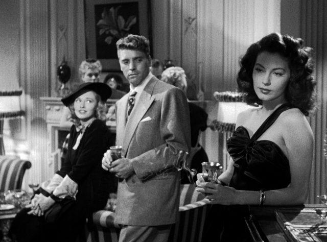 der Schwede (gespielt von Burt Lancaster) mit einer Freundin (gespielt von Virginia Christine) auf einer Party; er betrachtet Kitty Collins (gespielt von Ava Gardner), die elegant im Vordergrund steht