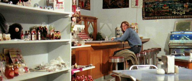 ein junger Mann sitzt an der Theke eines Cafés, Copyright: Universal
