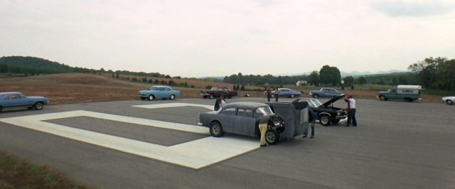 Chevrolet 1955 und ein muscle car mit geöffneten Motorhauben kurz vor einem Rennen