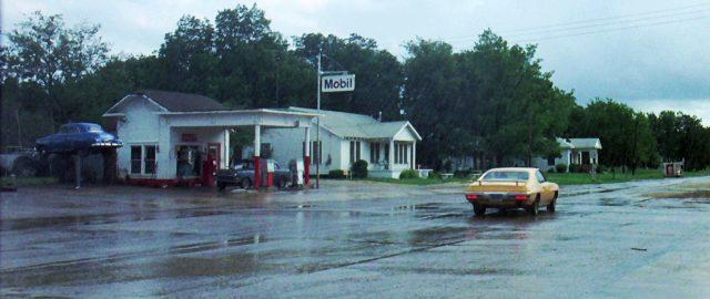 der Pontiac fährt auf einer verregneten Straße entlang einer Tankstelle, in welcher der 1955 Chevrolet steht, Copyright: Universal