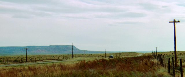 Fahrbahn, die sich bis zum Horizont erstreckt und an deren Seitenrändern Telegrafenmasten stehen, Copyright: Universal
