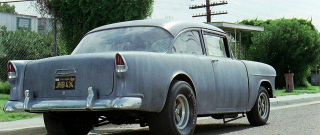 in einer Kleinstadt am Straßenrand geparkter 1955 Chevrolet von schräg hinten gezeigt, Copyright: Universal