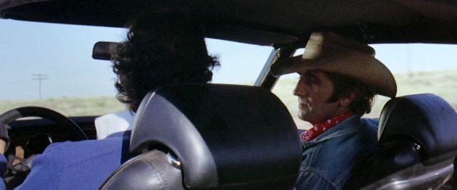 """Harry Dean Stanton als Anhalter im Cowboy-Outfit auf dem Beifahrersitz des """"GTO"""", Copyright: Universal"""