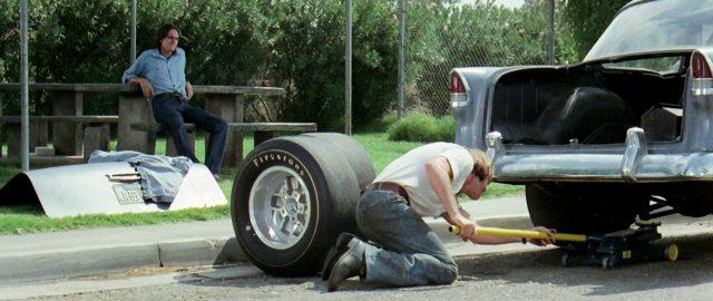 der Mechaniker (gespielt von Dennis Wilson) beim Reifenwechsel am Straßenrand in einer Kleinstadt, dem der Fahrer (gespielt von James Taylor) von einer Bank aus zusieht