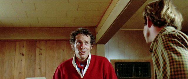 Warren Oates als G.T.O. im roten Kaschmirpullover in einer holzvertäfelten Bar, Copyright: Universal