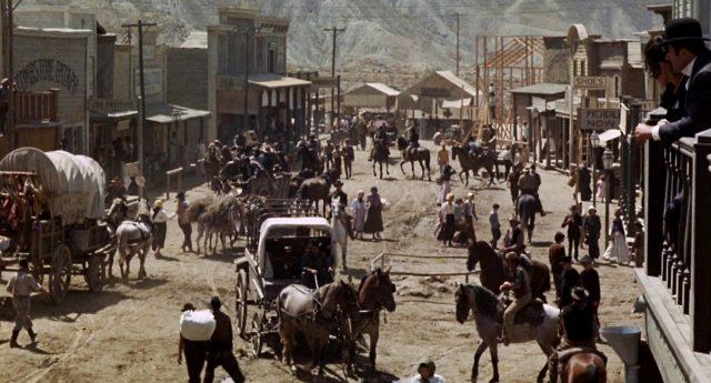 Blick auf die von Holzgebäuden gesäumte Hauptstraße von Tombstone, auf der geschäftiger Trubel mit Planwagen und Menschen herrscht