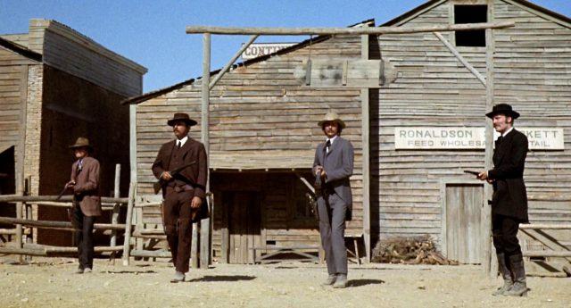 die Earp-Brüder und Holliday stehen bewaffnet am O.K. Corral