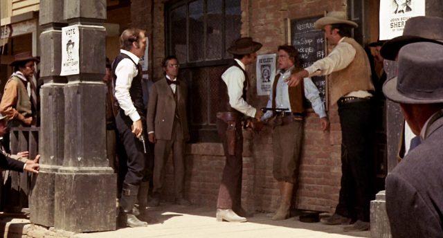 Wyatt Earp bedroht vor einem Restaurant The Kid mit einem Revolver