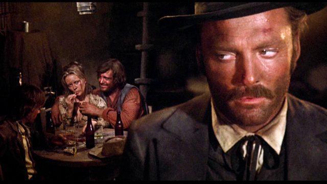 im Vordergrund steht Stacy Keach als Doc Holliday in der mexikanischen Kneipe, im Hintergrund sitzt an einem Tisch Katie Elder (gespielt von Faye Dunaway), die von Ike Clanton (gespielt von Michael Witney) begrapscht wird, Copyright: Frank Perry Films, Black Hill Pictures